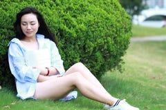 Lectura china de la muchacha en parque La mujer joven hermosa rubia con el libro se sienta en la hierba Imagen de archivo