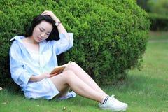 Lectura china de la muchacha en parque La mujer joven hermosa rubia con el libro se sienta en la hierba Foto de archivo libre de regalías