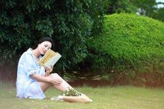 Lectura china de la muchacha en parque La mujer joven hermosa rubia con el libro se sienta en la hierba Imagenes de archivo