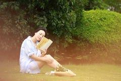 Lectura china de la muchacha en parque La mujer joven hermosa rubia con el libro se sienta en la hierba Fotos de archivo