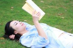 Lectura china de la muchacha en parque Mujer joven hermosa rubia con el lyingon del libro la hierba Fotos de archivo
