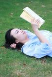 Lectura china de la muchacha en parque Mujer joven hermosa rubia con el lyingon del libro la hierba Imagenes de archivo