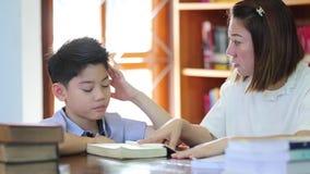 Lectura con el profesor - un escolar elemental lee en voz alta a su profesor almacen de video