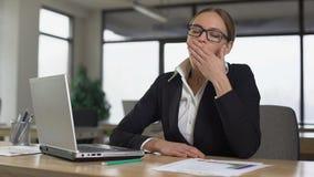 Lectura de bostezo del rato de la mujer en el ordenador portátil, cansado de trabajo monótono en oficina almacen de video