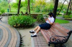 Lectura de la Alto-Colegiala en el parque Imagen de archivo libre de regalías
