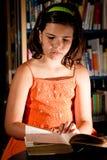 Lectura de la chica joven en biblioteca Foto de archivo libre de regalías