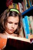 Lectura de la chica joven en biblioteca Imagen de archivo