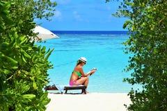 Lectura de la chica joven en la playa Maldivas imagenes de archivo