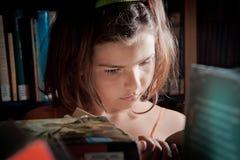Lectura de la chica joven en una biblioteca Fotografía de archivo