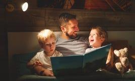 Lectura de la familia de la tarde el padre lee a niños libro antes del goin imagen de archivo libre de regalías