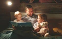 Lectura de la familia de la tarde el padre lee a niños libro antes del goin fotografía de archivo