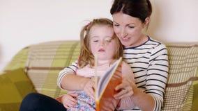 Lectura de la madre y de la hija en el sofá almacen de video