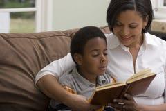 Lectura de la madre y del hijo en el sofá Fotografía de archivo