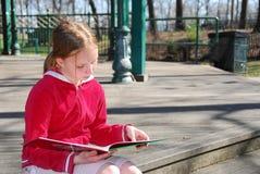 Lectura de la muchacha afuera Fotos de archivo
