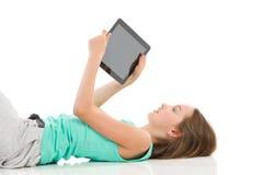 Lectura de la muchacha algo en una tableta digital Fotografía de archivo libre de regalías