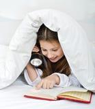 Lectura de la muchacha bajo la manta Fotos de archivo libres de regalías
