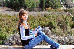Lectura de la muchacha del adolescente en el parque Fotos de archivo libres de regalías