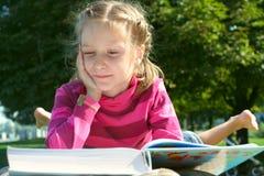 Lectura de la muchacha del niño en el parque Foto de archivo libre de regalías