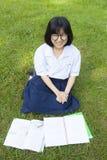 Lectura de la muchacha en el césped Imágenes de archivo libres de regalías