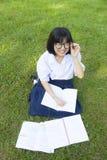 Lectura de la muchacha en el césped Foto de archivo libre de regalías