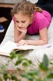 Lectura de la muchacha en el sofá Imagen de archivo