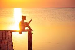 Lectura de la muchacha en el tiempo de la puesta del sol imágenes de archivo libres de regalías