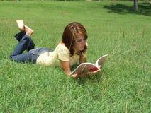 Lectura de la muchacha en la hierba Fotografía de archivo libre de regalías