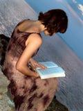 Lectura de la muchacha en la playa Fotos de archivo
