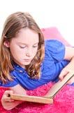 Lectura de la muchacha en las almohadillas Imagen de archivo
