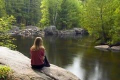 Lectura de la muchacha por el río Imagen de archivo libre de regalías