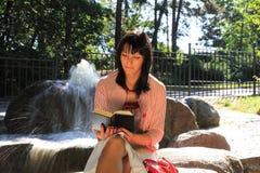 Lectura de la muchacha por la fuente Imagen de archivo libre de regalías