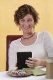 Lectura de la mujer adulta con los refrigerios Imagen de archivo libre de regalías