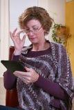 Lectura de la mujer adulta con los refrigerios Foto de archivo