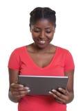 Lectura de la mujer africana en camisa roja con la tableta Imagenes de archivo