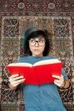 Lectura de la mujer bastante joven con el libro rojo Imagen de archivo