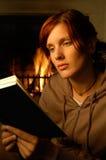 Lectura de la mujer (chimenea detrás) Imagen de archivo libre de regalías