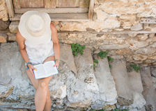 Lectura de la mujer de moda en una ciudad vieja Imágenes de archivo libres de regalías