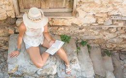 Lectura de la mujer de moda en una ciudad vieja Foto de archivo libre de regalías