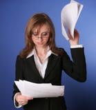 Lectura de la mujer de negocios impacientemente un fichero Imagenes de archivo
