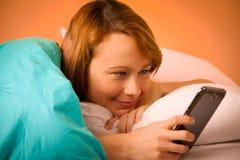 Lectura de la mujer de Preety SMS en el teléfono celular en cama fotografía de archivo
