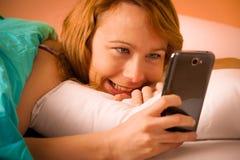 Lectura de la mujer de Preety SMS en el teléfono celular en cama imagenes de archivo