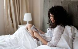 Lectura de la mujer en cama Fotografía de archivo libre de regalías