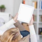 Lectura de la mujer en Ebook mientras que miente en el sofá imágenes de archivo libres de regalías