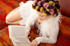 Lectura de la mujer en el sofá imagenes de archivo