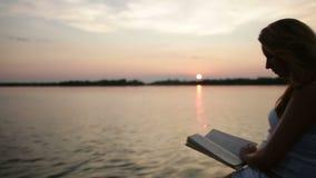 Lectura de la mujer en la puesta del sol almacen de video