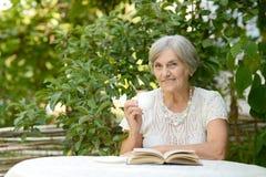 Lectura de la mujer en la tabla Imágenes de archivo libres de regalías