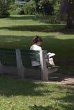 Lectura de la mujer en Park_7905-1S Foto de archivo libre de regalías