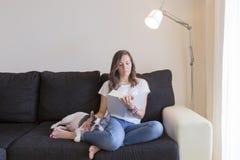 Lectura de la mujer en un sofá Foto de archivo libre de regalías