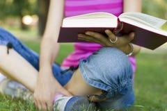 Lectura de la mujer joven al aire libre Imágenes de archivo libres de regalías
