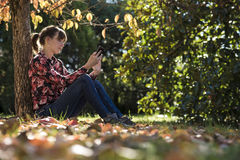 Lectura de la mujer joven algo en un dispositivo digital Foto de archivo